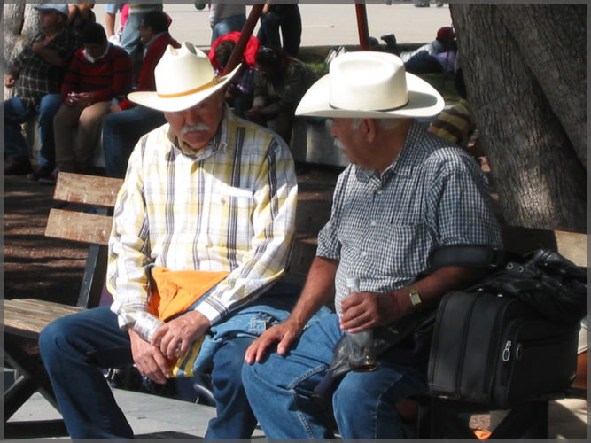 Two men talking on a bench in the Ajijic plaza.