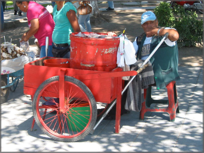 Man selling ice cream from a red cart on the malecon in the town of Chapala, on Lake Chapala.