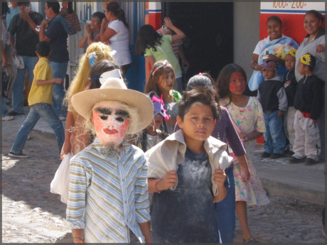 Masked and flour drenched children in Carnaval parade.