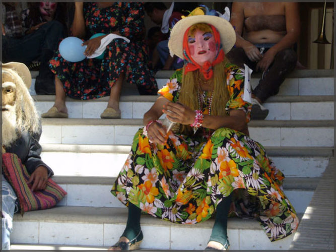 Person in flowered dress and mask rests on the steps after the Mardi Gras parade in Ajijic.