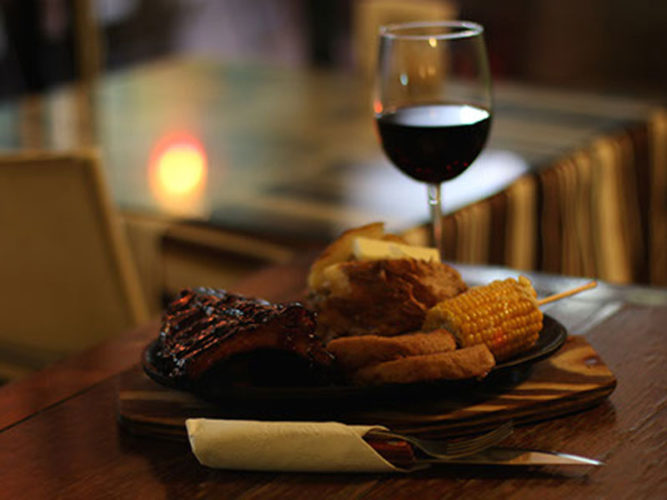 Plate of food and glass of wine at Bruno's Steakhouse, one of the many Ajijic Restaurants serving grilled meat.