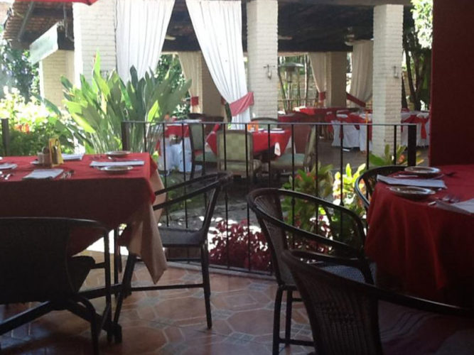 Dining area at Ajijic restuarant, Roberto's with red clothed tables and white draped pilars.