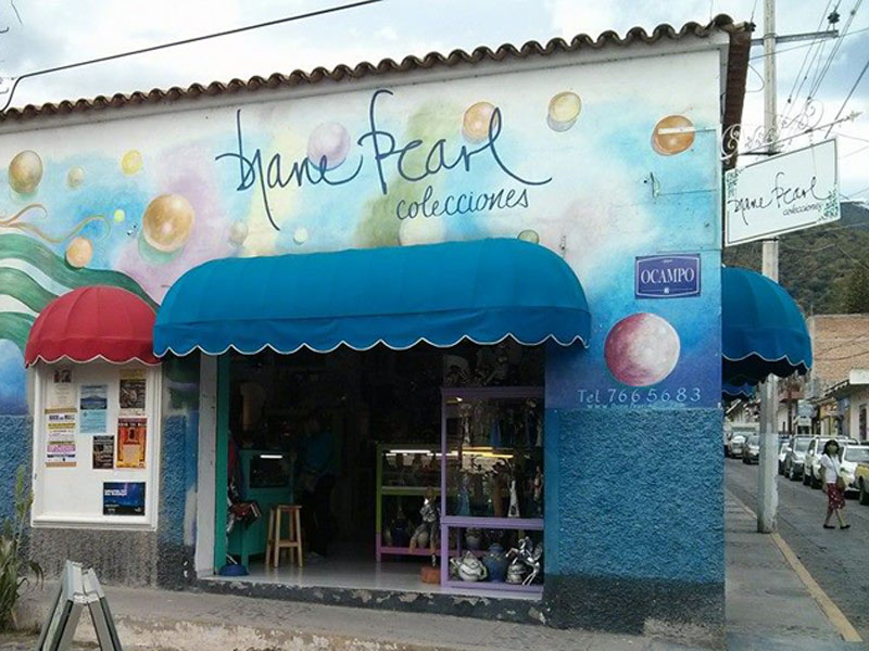 Street view of Diane Pearl Clecciones with blue and red awnings and bubbles painted on the wall.