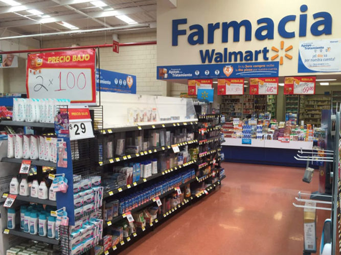 blue farmacia walmart sign above pharmacy counter with shelves of stock in front