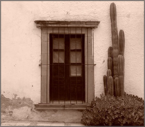 Artist Damyn Young photo of Black and white image of an old mexican window in a stucco wall.