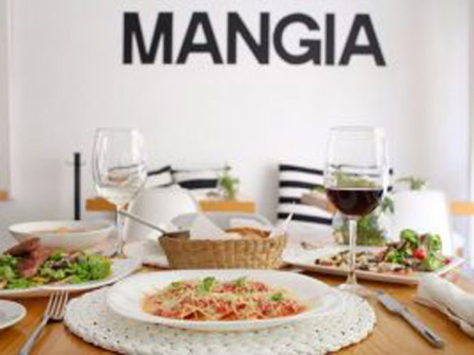 A newer Ajijic Restaurant with a plates of food of the table and mangia written on wall at Alex's Pasta Bar.