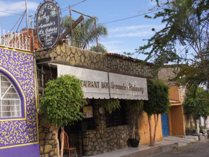 armandos hideaway restaurant street view with white awnings and stone wall, an established Ajijic restaurant.