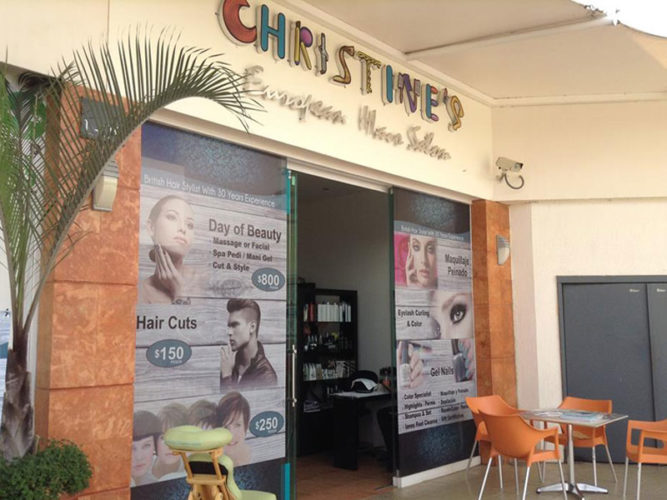 christine's hair salon storefront with posters in window advertising a variety of services a table and four chairs directly in front