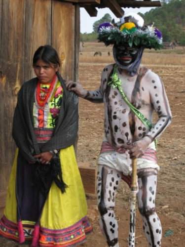 Traditionally dressed Huichol woman and man with totally painted body symbolizing the rich Ajijic history.
