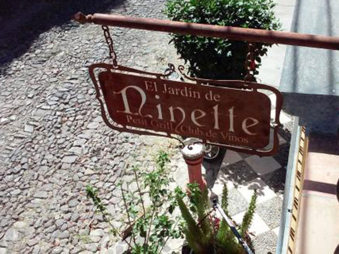 Ajijic Restaurant El Jardin de Ninette's wrought iron sign hanging over sidewalk and cobble stone road.