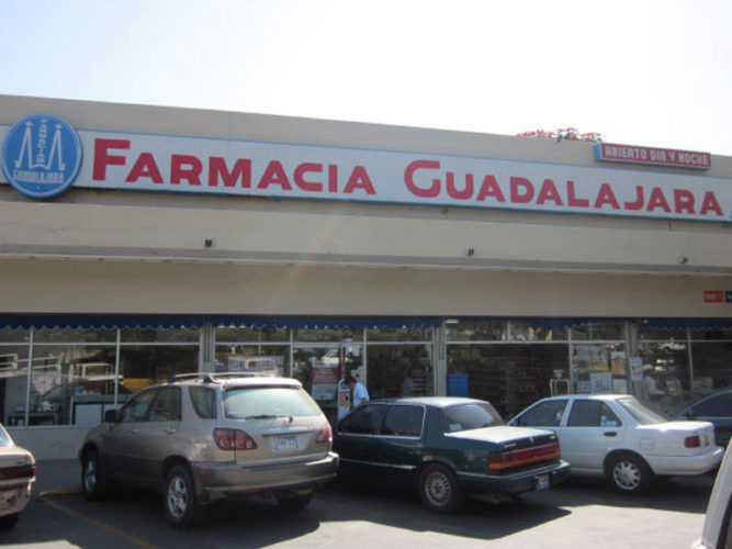 farmacia guadalajara sign above windowed storefront and cars parked in front