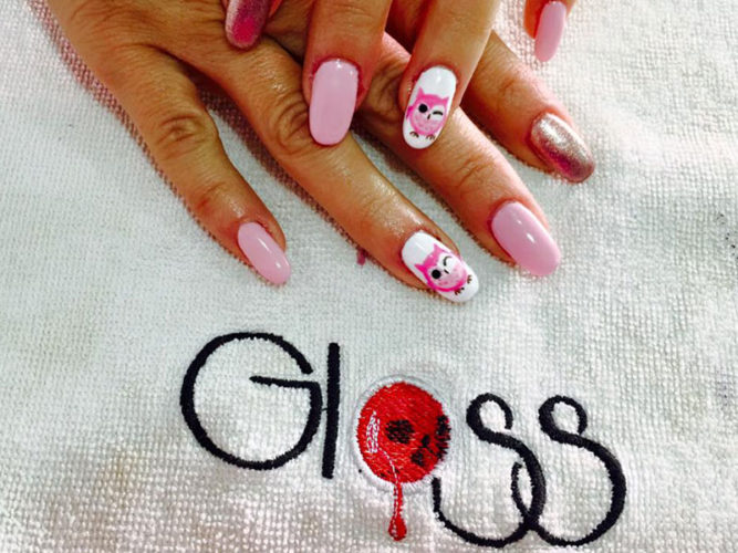 two ladies hands with pink manicured nails on a white towel with the word Gloss embroidered on it