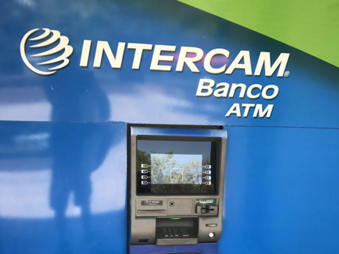 intercam banco atm inset on a bright blue wall with white corporate lettering and logo above it