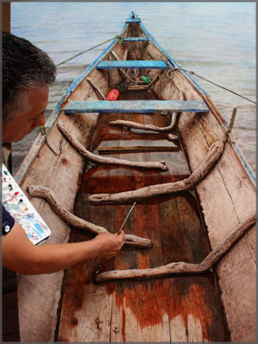 Artist Javier Ramos painting an oil on canvas of the inside of an old canoe .