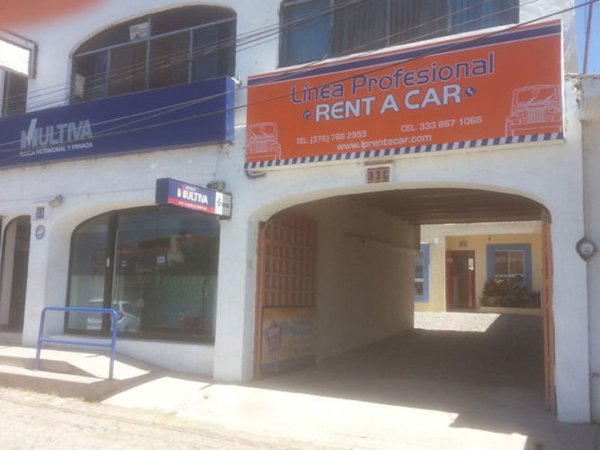 orange blue and white linea profesional rent a car sign above large archway entrance to building