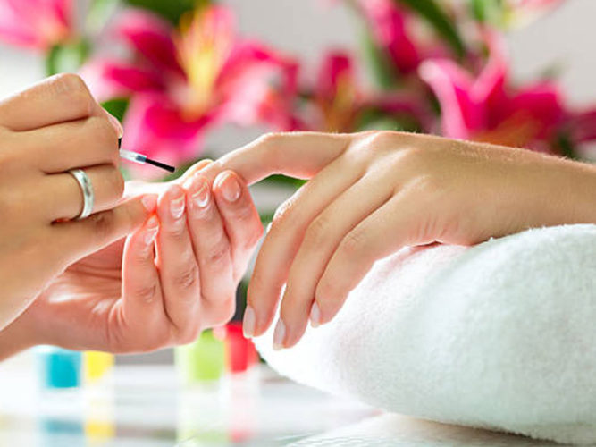female hands painting nails of another female hand on rolled up white towel blurred image of pink lily's in background