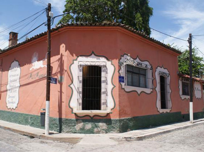 Street view of Mi Mexico corner shop with pink walls and white scrolled frames painted around windows