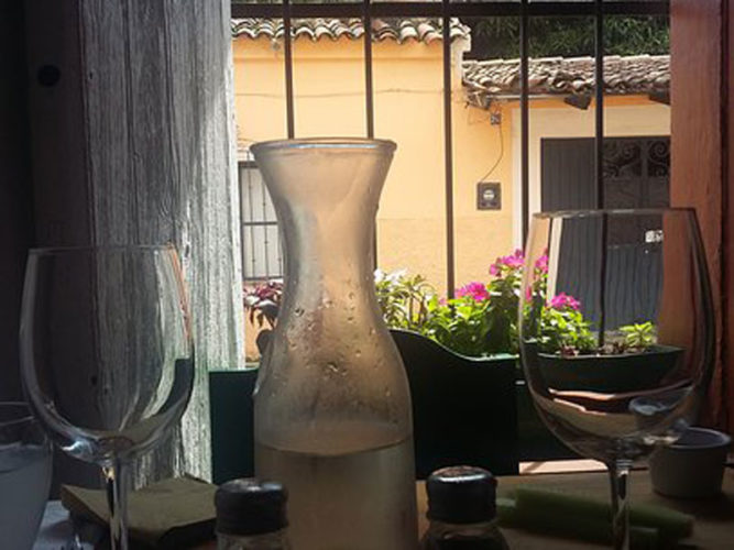 Two wine glasses and frosty carafe on the table at Ajijic restaurant Pasta Trenta.