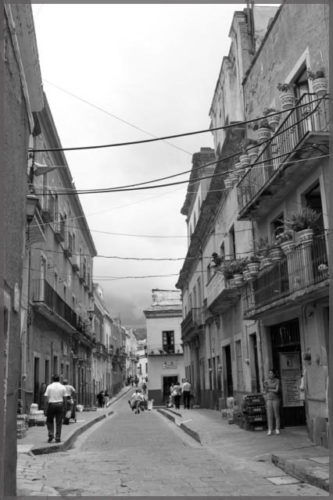 Mexican street with buildings on both sides in black and white by artist Damyn Young.