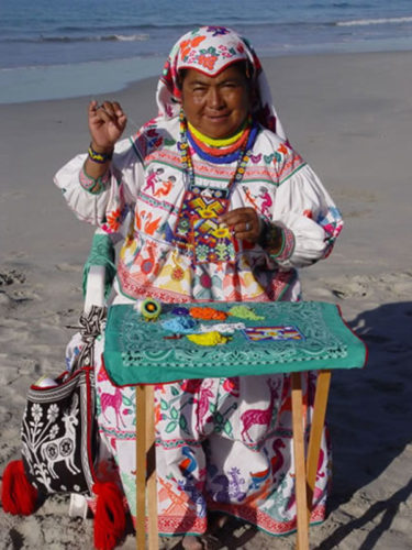 Traditionally dressed woman sitting on chair on the sand sewing with beads.