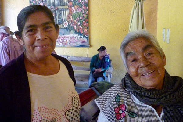 Two elderly woman leaving with their dispensas with big smiles on their faces.