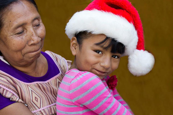 Little girl with Santa hat sitting on her grandmothers lap.