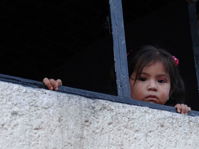 Little girl looking down to the street from window in Ajijic.