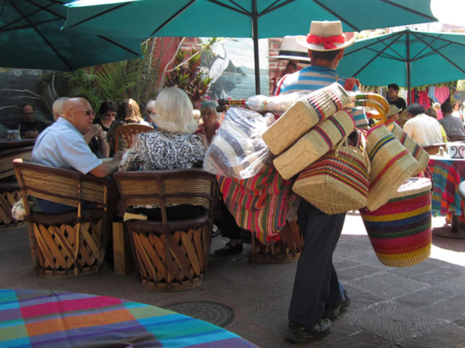 Example of Ajijic people walking with woven purses and baskets for sale in the Ajijic plaza.