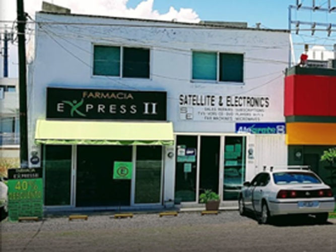 street view of farmacia express store with black white and yellow sign on white brick wall and open sliding glass doors