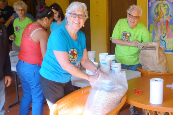 Operation Feed volunteers packing beans and rice in bags for dispensing.